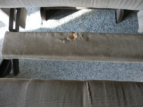The broken spring put a hole in the board between the foot rest and the seat.