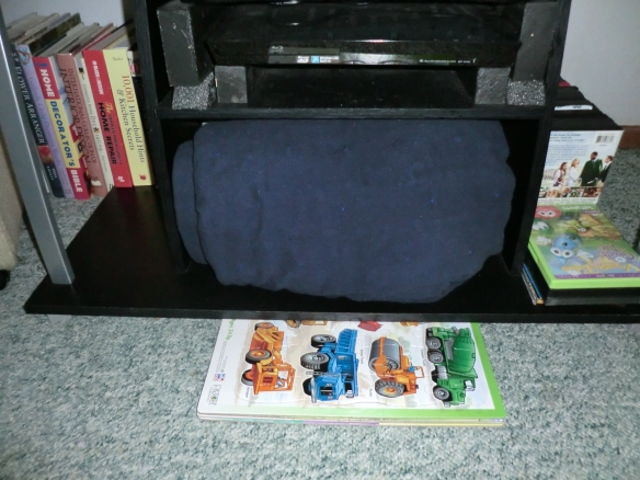 Cardboard puzzles slide easily under the TV stand.