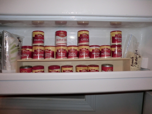 Less frequently used spices are stored inside a shelf organizer set on its side.