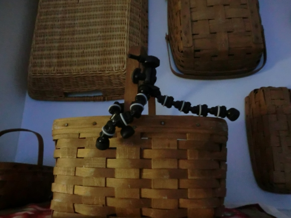 Flexible legs tripod attached to the handle of a basket.