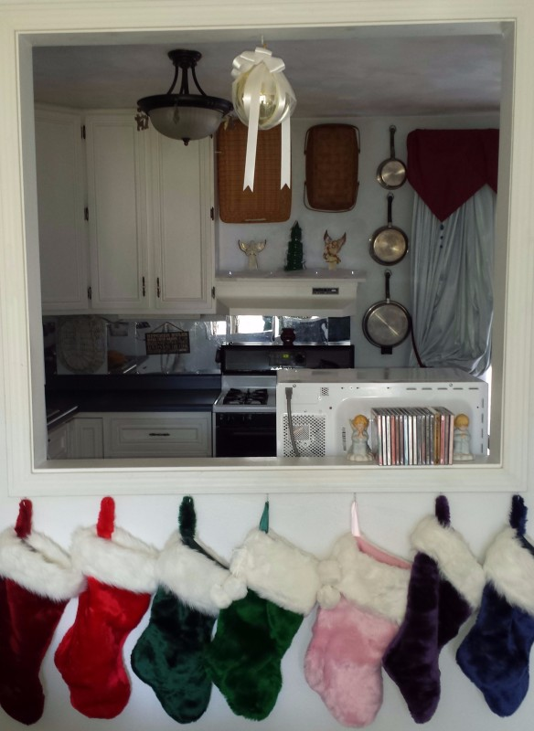 The stockings hang from the window between the kitchen and the living room since I don't have a mantle. I stick my Christmas cards around the molding of the window. I made the kissing ball out of a gold ornament, tulle, and white ribbon.