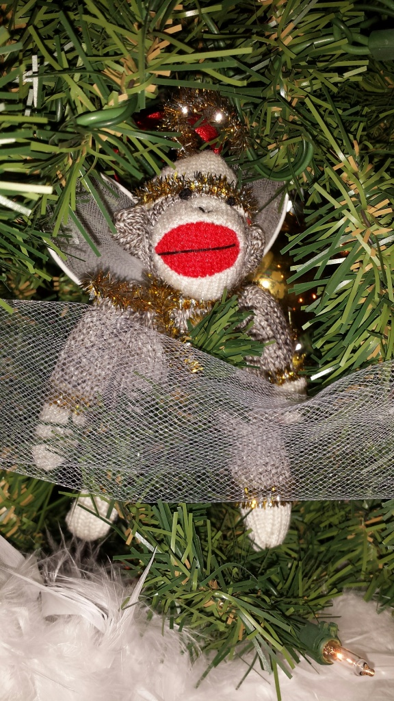 This angel was purchased in memory of my dad who I remember wearing monkey socks when I was a child. The year of his death is written on it. I also have a sweet, ivory angel in memory of David's mom. Since the monkey sock did not fit with my theme, I nestled him inside the branch.