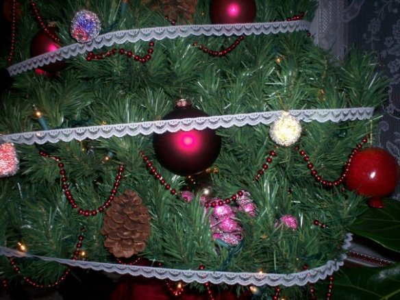 """Beaded fruit, pine cone """"nuts,"""" drizzled with icing made from a lace garland."""