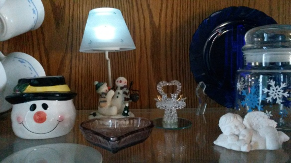 Flame-less tea lights in lamp displayed in a china cabinet.