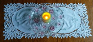 Candle on glass plate over table runner.