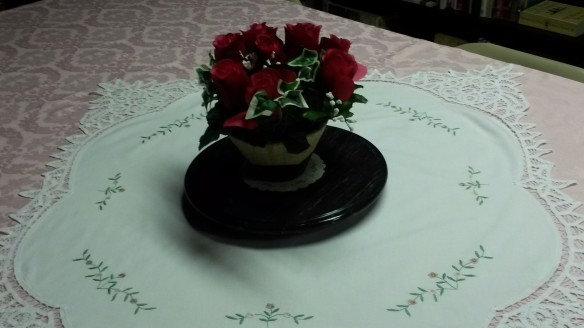 Floral arrangement on tablecloth.