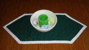 Candle in bowl on table runner