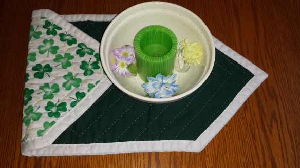 Candle in bowl with flowers on table runner